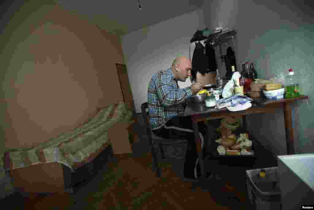 Matovic eats a meal in his makeshift home.
