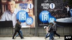 Парламент сайлауына кандидаттардың бірі Хашим Тачидің суреті ілініп тұрған көшеде кетіп бара жатқан адамдар. Приштина, 4 маусым 2014 жыл.