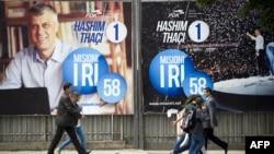 Люди проходят мимо предвыборных плакатов. Приштина, 4 июня 2014 года.