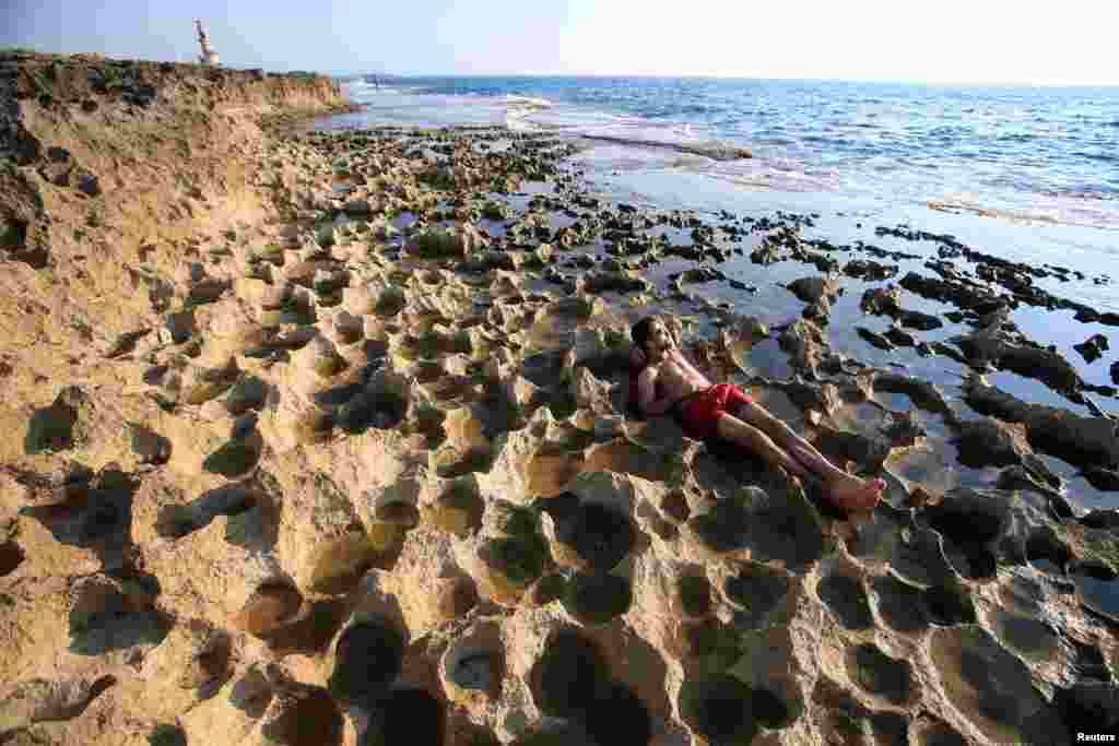 A man enjoys the beach on a tiny island in Sidon, southern Lebanon. (Reuters/Ali Hashisho)