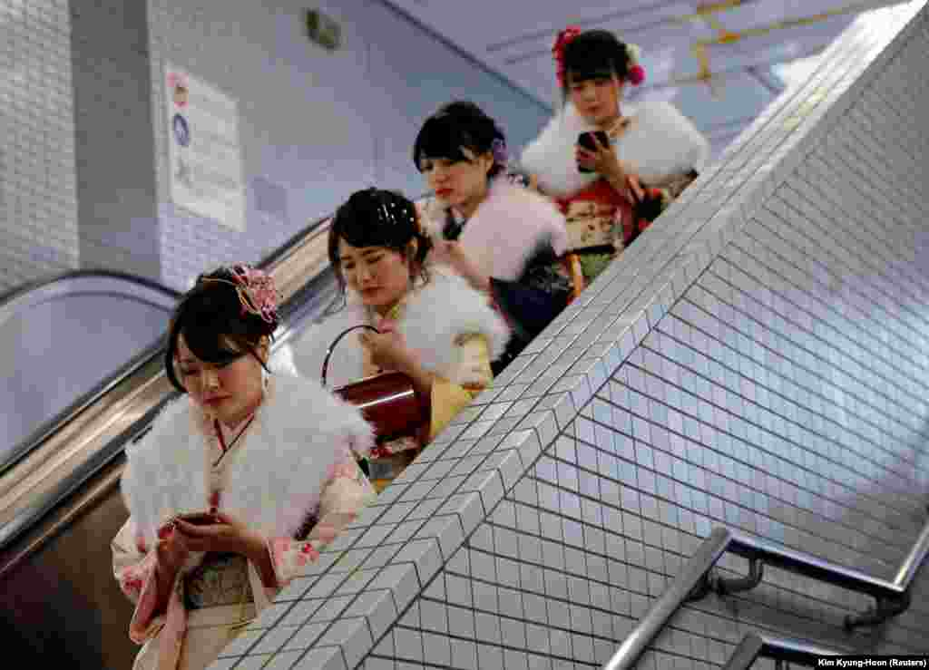 Japanese women wearing kimonos ride an escalator at a subway station after attending their Coming of Age Day ceremony in Tokyo. (Reuters/Kim Kyung-Hoon)