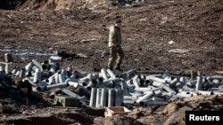 Мужчина в камуфляже идет по полю, на котором могли остаться боеприпасы украинской армии, выведенной из Дебальцева. 22 февраля 2015 года.