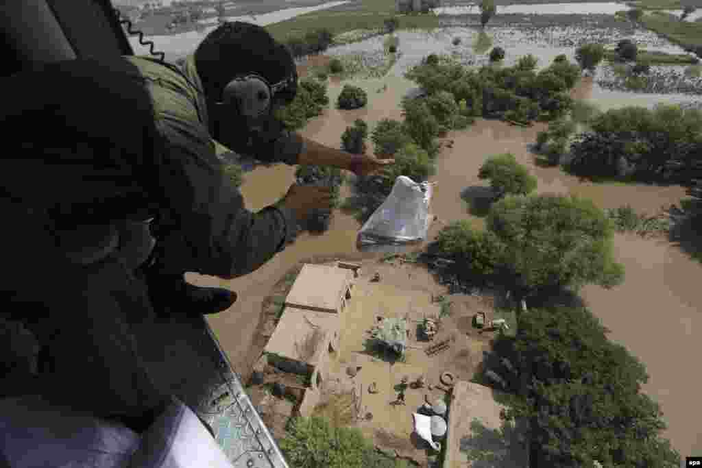 A Pakistani Army soldier distributes food bags from a helicopter in flooded areas in Shujabad, on the outskirts of Multan. Hundreds have died from flooding. (epa/Omer Saleem)