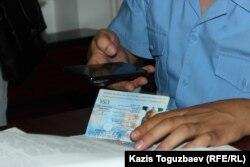 Прокурор Еркін Баймағамбетов өзінің ұялы телефонына америкалық адвокат Джаред Генсердің төлқұжатын суретке түсіріп отыр.