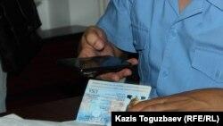 Прокурор Еркин Баймагамбетов фотографирует паспорт американского адвоката Джареда Генсера на свой мобильный телефон.