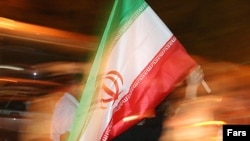 A supporter of Iranian President Mahmud Ahmadinejad waves the national flag in Tehran at a rally ahead of the vote.