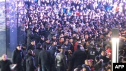 Дүкенге кезекке тұрған халықты полиция тежеп тұр. Пекин, 13 қаңтар 2012 жыл.