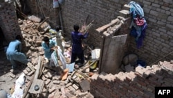 Earthquake survivors remove their belongings from the rubble of a damaged house in southern Pakistan (file photo).