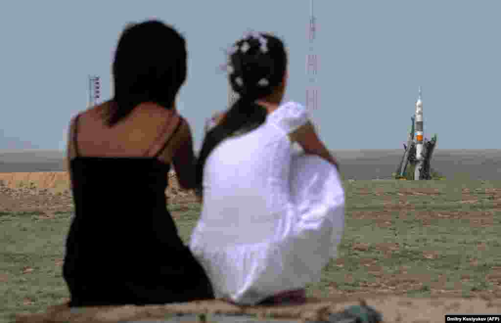 Kazakh girls watch as a Soyuz rocket prepares for launch in 2009. As work continues on Russia's troubled Vostochny Cosmodrome and SpaceX aims to ferry astronauts to the ISS from U.S. soil beginning on May 27, Kazakhstan's aging launch facility and the population it supports is likely to be left behind.