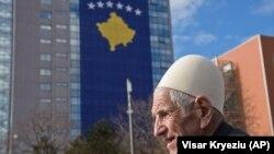 Një burrë kalon pranë Qeverisë së Kosovës, në ndërtesën e së cilës është vendosur flamuri shtetëror, për nderë të dhjetëvjetorit të pavarësisë.