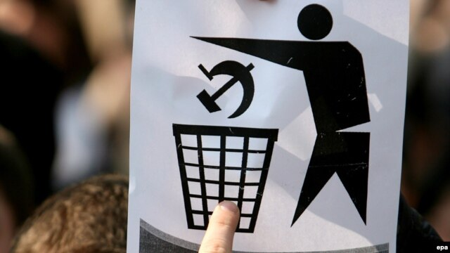 A student shows an anticommunist sign during protests in Chisinau