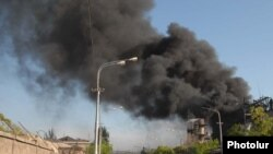 Armenia -- Onlookers watch as black smoke billows from the Nairit chemical plant in Yerevan hit by an explosion on 14May2009