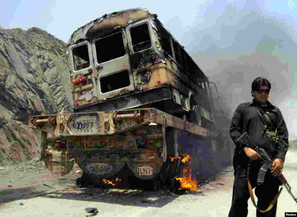 A tribal policeman stands guard near a burning NATO supply convoy in the Khyber tribal region of Pakistan. Militants armed with rocket launchers and sophisticated weapons attacked three NATO supply trucks close to the Pakistan-Afghan border, killing six. (Reuters/Shahid Shinwari)