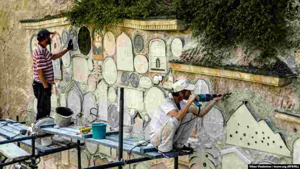 Рабочие реставрируют барельефы