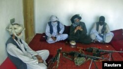 Taliban fighters pose with weapons as they sit in a room at an undisclosed location in southern Afghanistan in April 2011.