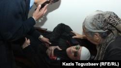 Полицейские положили подсудимого по делу «джихадистов» Оралбека Омырова на скамейку в зале судебного заседания в Алмалинском районном суде и думают над тем, как оказать ему помощь. Алматы, 16 октября 2018 года.