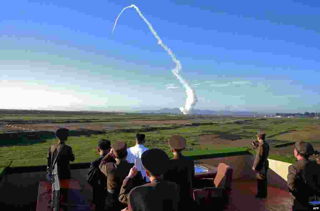 North Korean leader Kim Jong-Un (center, in white shirt) watches the test of a new missile system at an undisclosed location on May 28. (AFP)