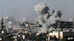A video grab shows smoke billowing from a building in the Jouret Sheikh neighborhood of the restive central city of Homs on July 1.