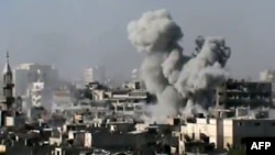 Syria -- A video grab shows smoke billowing from a building in the Jouret Sheikh neighbourhood of the restive central city of Homs, 01Jul2012