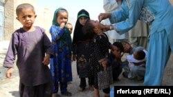 آرشیف: یک واکسیناتور در حال تطبیق واکسین به کودکان