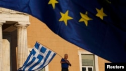 Мужчина с флагом Греции перед зданием парламента. Афины, 22 июня 2015 года.