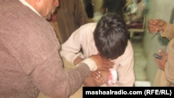 A man holds an injured relative after an explosion in Peshawar during a funeral ceremony killed at least 15.
