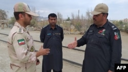 In this photo taken on October 16, 2018, a Pakistani border security official (R) and an Iranian border official meet at Zero Point in the Pakistan-Iran border town of Taftan.