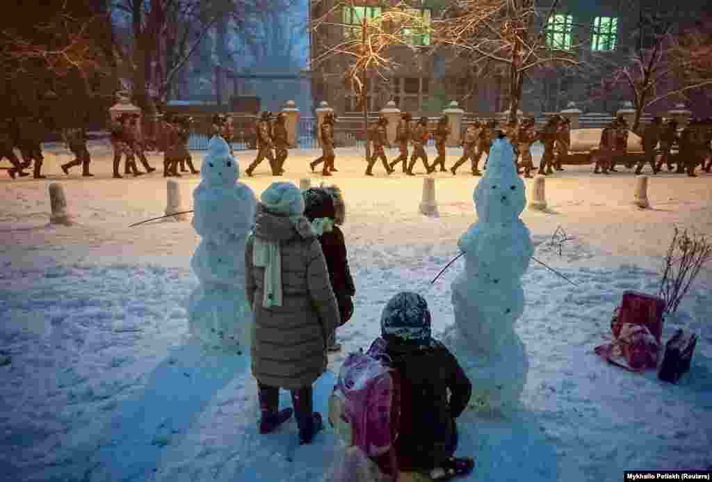 Children play in the snow as riot police move to block protests near the presidential administration building.