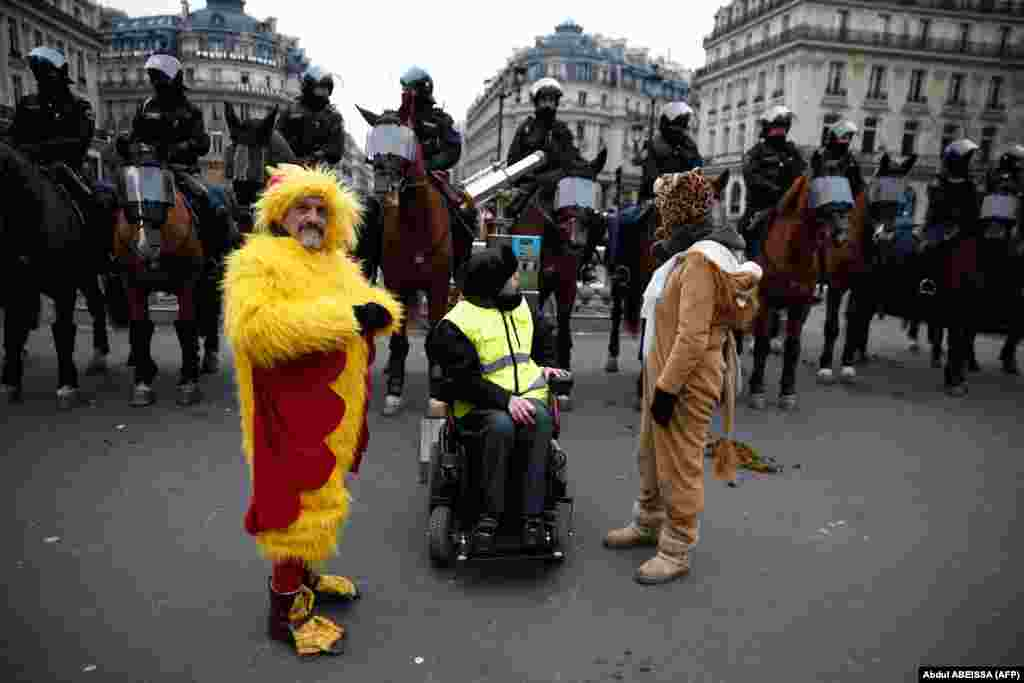 Protesters stand in front of mounted police during a demonstration in front of the Opera House in Paris against rising costs of living blamed on high taxes on December 15. (AFP/Abdul Abeissa)