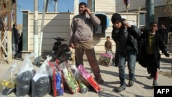 Iraqis who fled violence in Fallujah collect aid supplies in Karbala on January 9.