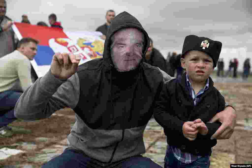 A Serb with a child wears a face mask depicting Serbian war criminal Ratko Mladic as he participates in a ceremony commemorating a medieval battle with invading Ottoman forces in 1389 at Gazimestan, Kosovo. Hundreds of Serbs gathered to mark the 629th anniversary of the battle in which a Serbian army was defeated by the Ottoman Empire. (AP/Visar Kryeziu)