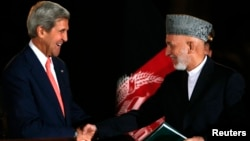 Afghan President Hamid Karzai (right) shakes hands with U.S. Secretary of State John Kerry after a news conference in Kabul on October 12.