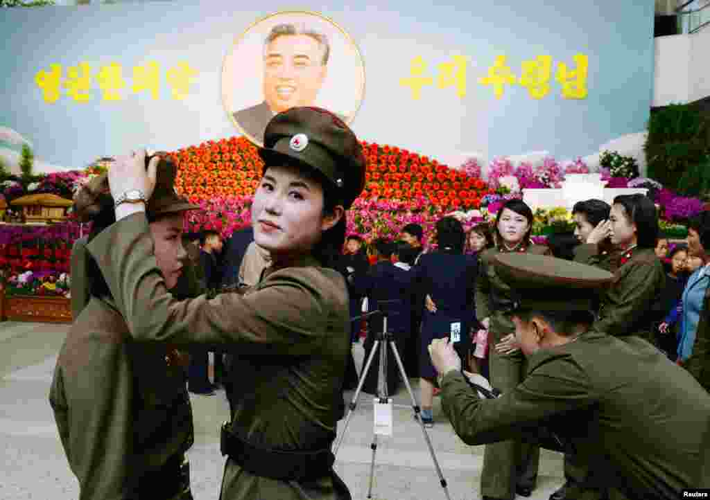 North Korean female soldiers prepare to take a commemorative photograph in front of a flower exhibition featuring North Korea's late founder Kim Il Sung in Pyongyang. (Reuters/Kyodo)