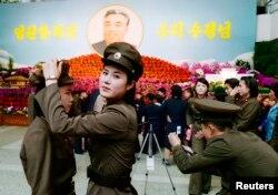 Женщины в солдатской форме собираются установить портрет вождя на цветочной выставке, северная Корея, апрель 2014