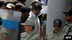 Former Pakistani President Pervez Musharraf (center) was escorted by soldiers as he arrived in court in Islamabad on April 12.