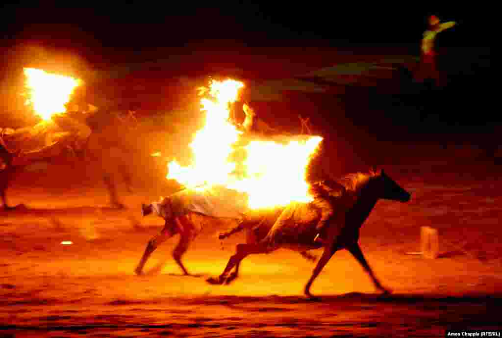 Flaming horsemen gallop through the opening ceremony. The games are devoted to traditional sports of Central Asia.