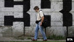 Мъж с предпазен шлем минава покрай графит в София