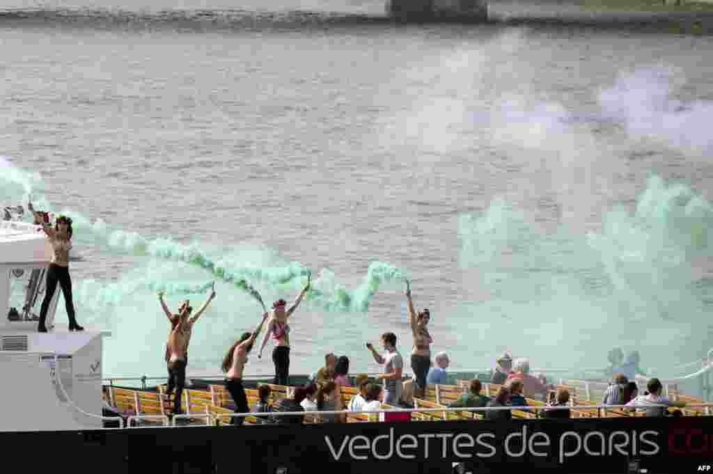 """Femen тобының мүшелері Ресейде ұсталған """"Гринпис"""" қозғалысының белсенділерін қолдау акциясында тұр. Париж, қыркүйек, 2013 жыл."""