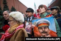 A woman holds a portrait of Josef Stalin near the Kremlin as people gather in December 2017 to mark the anniversary of the dictator's birth.
