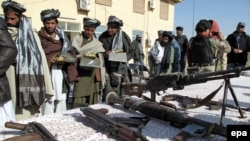 A group of former Taliban militants receive clothes and copies of the Koran as they surrender their weapons during a reconciliation ceremony in Helmand late last year.