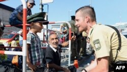 A German police officer and a migrant boy share a lighter moment after the latter's arrival at the main train station in Munich. Germany is expected to receive hundreds of thousands of asylum-seekers this year.