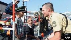 Nje polic gjerman duke zbavitur një fëmijë migrant në Munich, 1 shtator 2015