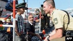Німецький поліцейський та хлопчик-біженець жартують, поки мігранти очікують на автобус, який забере їх із залізничного вокзалу, Німеччина, 1 вересня 2015 року