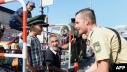 Мюнхенде неміс полицей сириялық босқын баламен сөйлесіп, басына өзінің бас киімін кигізіп тұр. Германия, қыркүйек 2015 жыл.