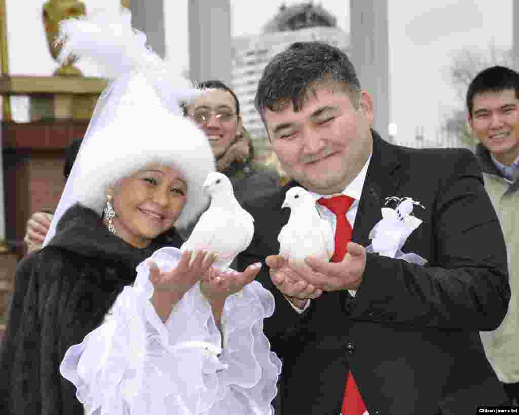 A newly married couple prepares to release a pair of doves, which is seen as a symbol of a happy life.