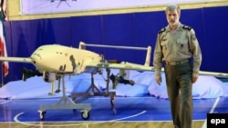 Iranian Deputy Defense Minister Brigadier General Amir Hatami poses with a new, locally made combat drone during an unveiling ceremony in Tehran on September 23.