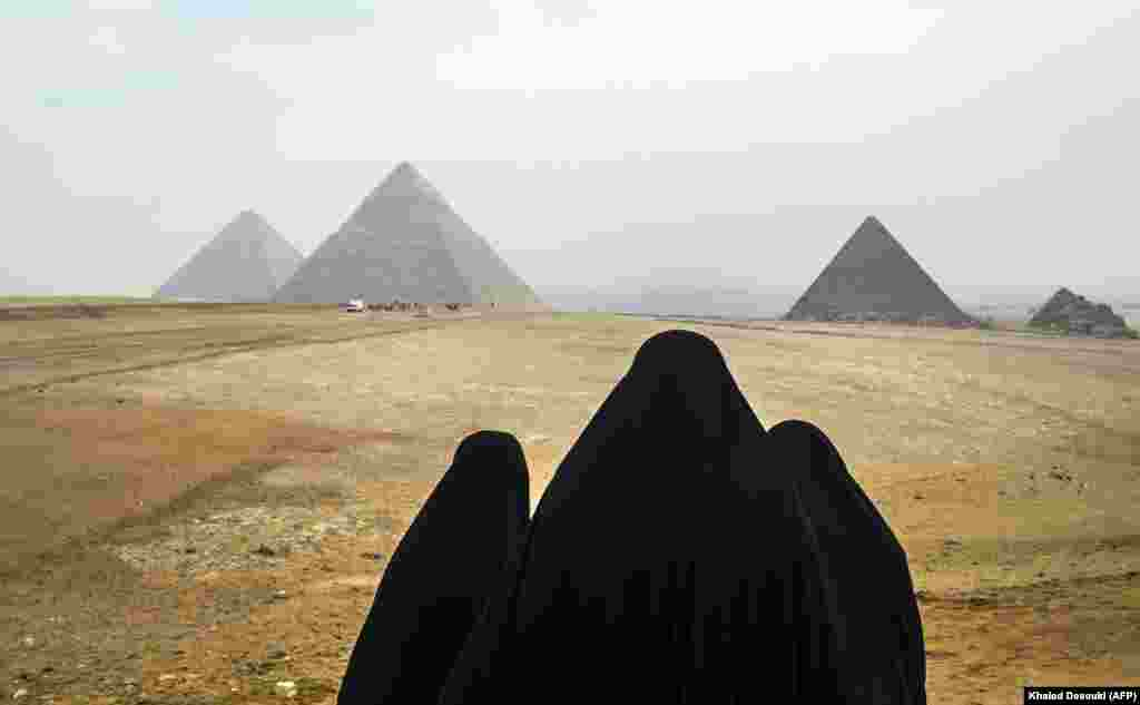 Women wearing veils look at the Great Pyramids of Giza on the southwestern outskirts of the Egyptian capital Cairo. (AFP/Khaled Desouki)