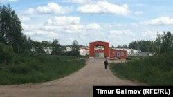 Охранник спешит отогнать журналистов, снимающих свинокомплекс