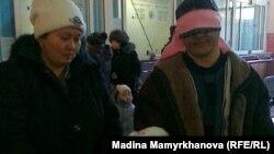 Исраил Азнабкиев отбасымен бірге Астана қаласының темір жол вокзалында тұр. 1 ақпан 2012 жыл.