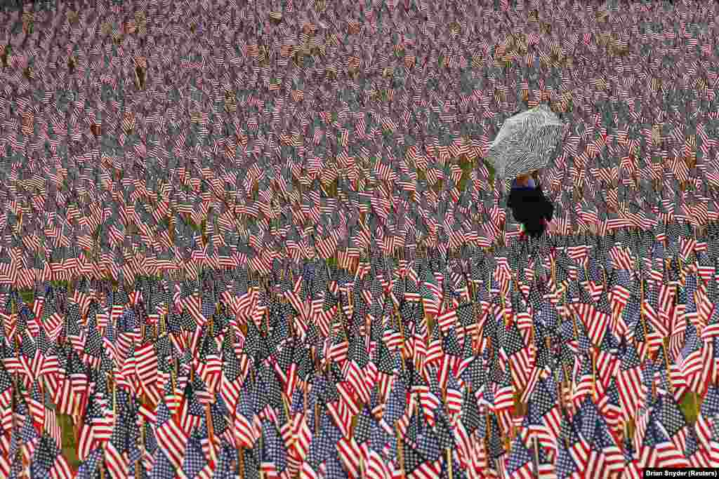 A pedestrian carrying an umbrella walks through a Memorial Day display of United States flags on the Boston Common in Boston, Massachusetts. (Reuters/Brian Snyder)